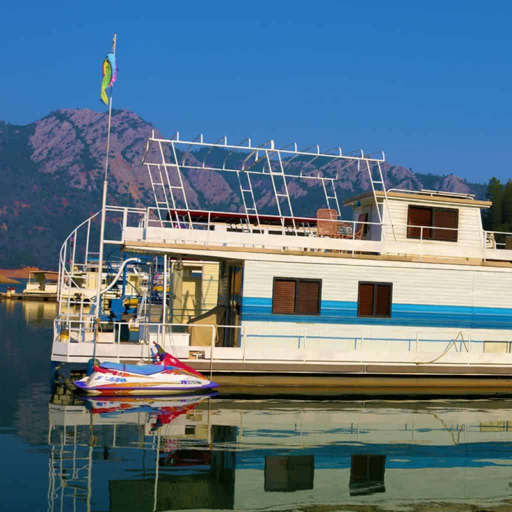Houseboat on a lake with mountains in the background and a jet ski parked next to it