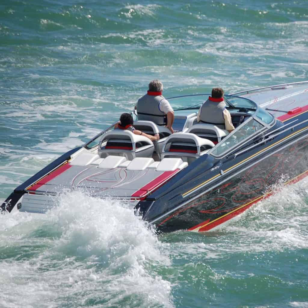Black speedboat with read accents and four seats cruising with three people onboard